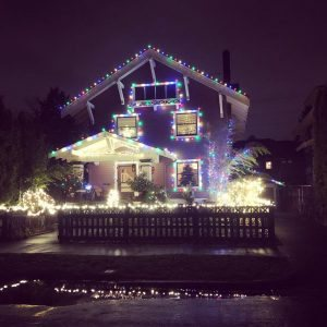 house at night with colorful christmas lights reflecting in a puddle