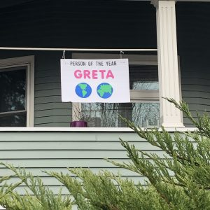 sign in front of house shows globes and Greta Person of the Year