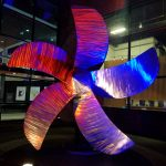 large brushed steel fan blade colored by red and blue lights at night