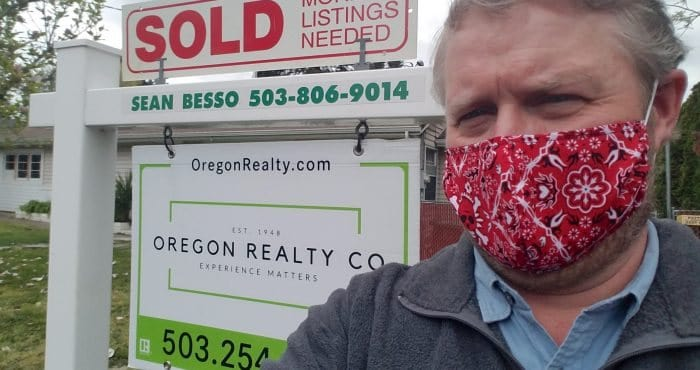 man standing in front of real estate sign wearing a protective mask