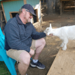 man petting goat